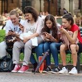 dzieci siedza na lawce z telefonami
